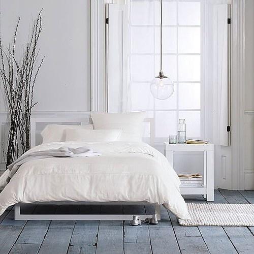 una semplice camera da letto nordica con un pavimento in legno imbiancato, una lampada a sospensione, mobili bianchi moderni e una disposizione dei rami