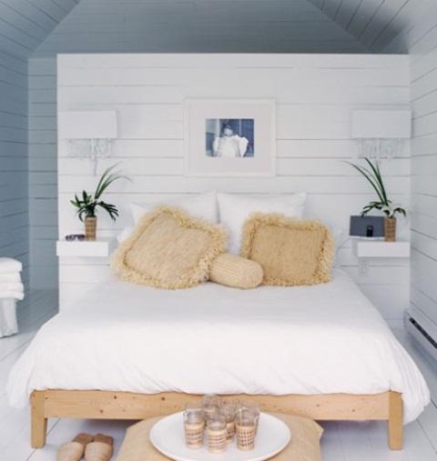 un Noridc incontra la camera da letto costiera fatta in bianco e blu, con un letto in legno e tocchi di vimini più vegetazione in vaso