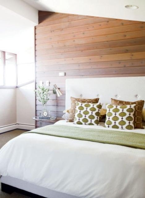 un'accogliente camera da letto decorata con una parete in legno colorato, un letto bianco imbottito e cuscini stampati