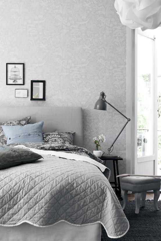 una camera da letto nordica in grigio, con carta da parati stampata, un letto grigio imbottito, biancheria da letto stampata e un comodino
