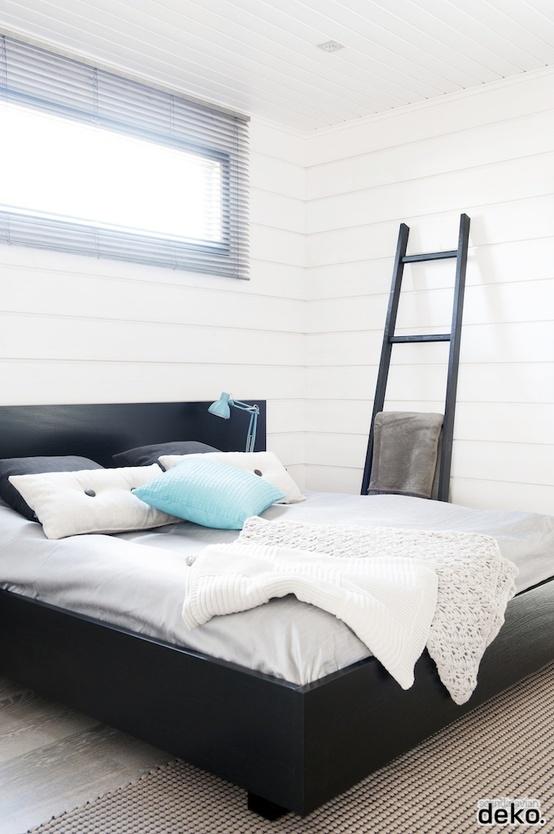 una camera da letto tranquilla fatta con battiscopa bianco, un letto nero per un contrasto, una scala nera e tocchi di azzurro