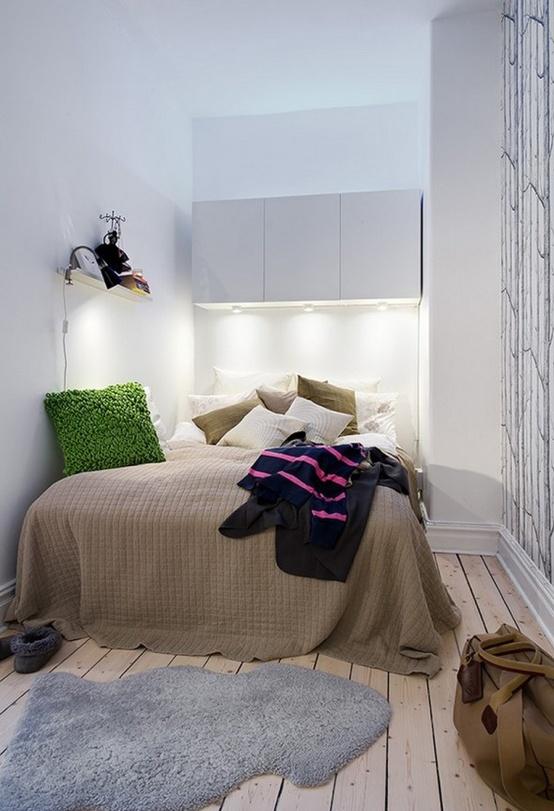una piccola camera da letto scandinava con superfici bianche lucide, un pavimento in legno, un letto comodo e lenzuola luminose