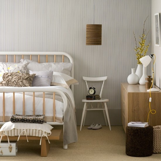 una camera da letto nordica con carta da parati stampata, mobili retrò, lampade, panche e uno sgabello