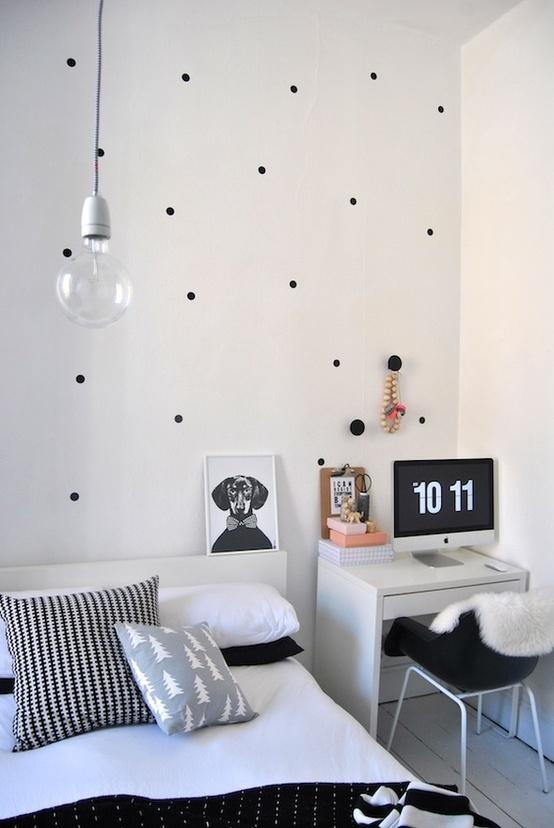 una camera da letto nordica monocromatica fatta con alcune stampe, un letto, una scrivania e una lampadina