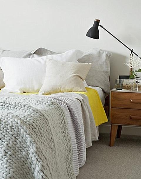 una camera da letto nordica con biancheria da letto neutra, un comodino in legno, una lampada nera
