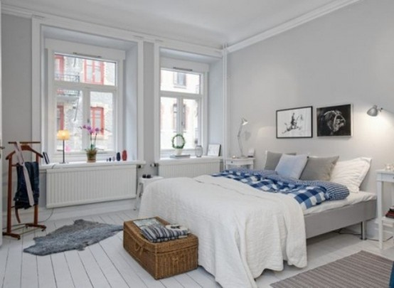 una camera da letto nordica ariosa con un letto grigio, un cestino per riporre e alcuni mobili retrò