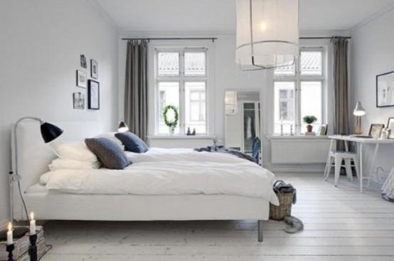 una camera da letto monocromatica ariosa con una lampada a sospensione, un letto imbottito bianco, biancheria da letto neutra e lampade e luci