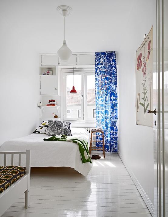 una camera da letto scandinava minimale ariosa con un letto bianco, contenitori incorporati e tessuti luminosi