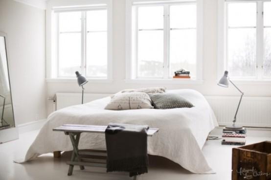 una camera da letto ariosa e luminosa con un letto, una panca, alcune lampade e molta luce naturale