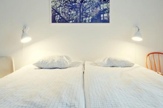 una camera da letto nordica con sedie e letti, lampade da parete e un'opera d'arte luminosa