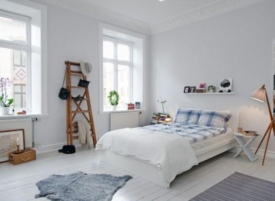 una camera da letto scandinava ariosa con pareti bianche e pavimento, mobili e lampade rustici vintage e vegetazione