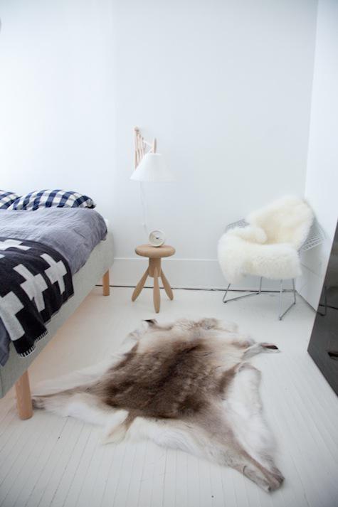 una camera da letto nordica con un letto in legno, biancheria da letto grafica e un sacco di pelliccia sintetica per l'intimità