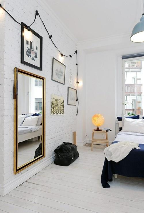 una camera da letto nordica con pareti in mattoni bianchi, una galleria a muro con specchi e opere d'arte, un letto e sgabelli a gradini come comodini
