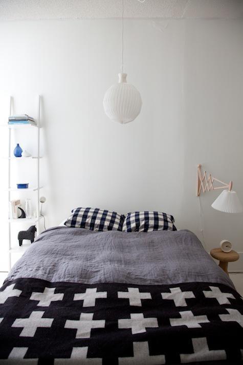 una camera da letto scandinava con mobili semplici e minimal, biancheria da letto grafica e una lampada a sospensione