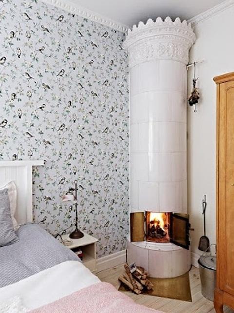 una camera da letto nordica ariosa con carta da parati floreale, una stufa bianca e lenzuola color pastello