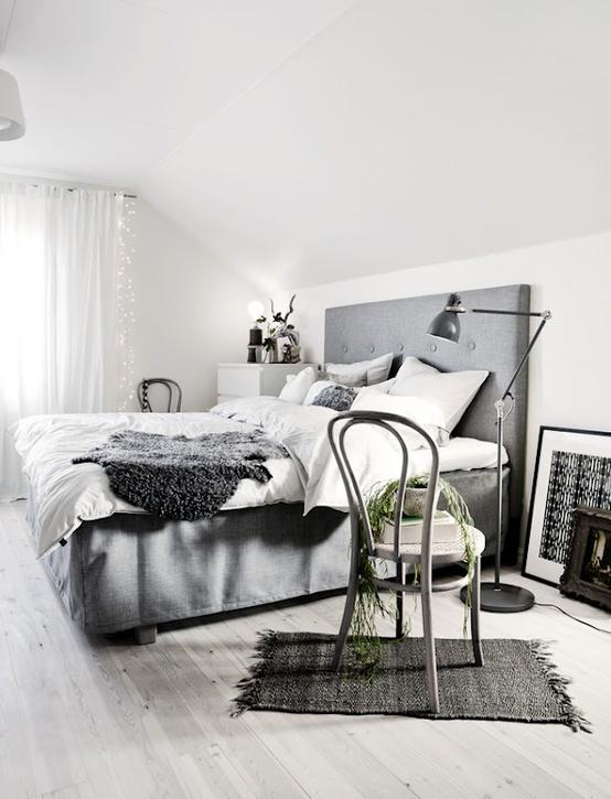 una camera scandinava con un letto grigio, alcuni mobili retrò, lampade e luci appese alla finestra