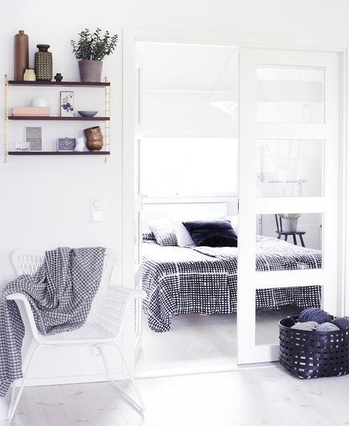 una piccola camera da letto nordica con un letto bianco, biancheria da letto grafica, lucernari e sedie come comodini