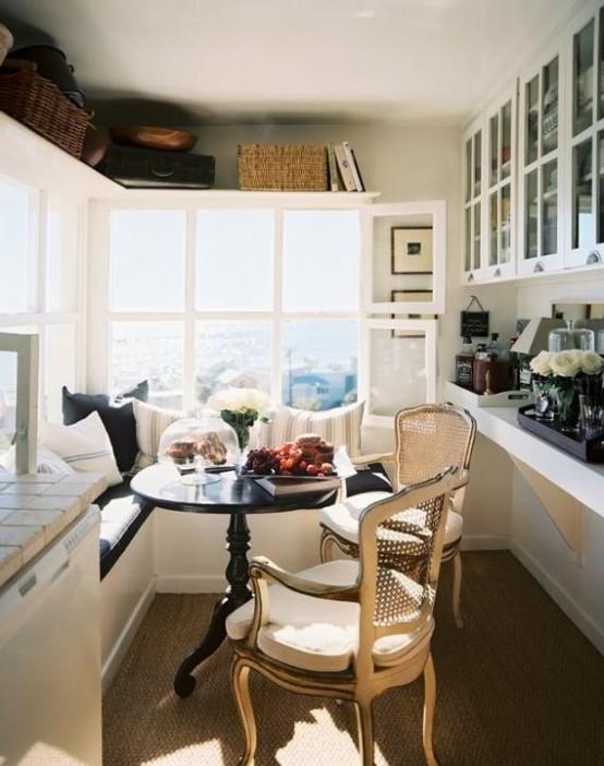 una piccola cucina rustica con vista, una panca a L, un tavolo rotondo, sedie vintage, vetrine e mensole