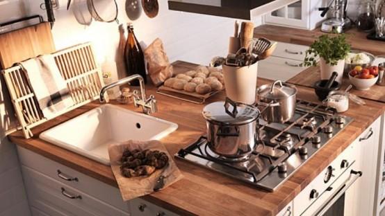 una piccola cucina con armadi bianchi, ripiani in macelleria macchiati e hardware blakc