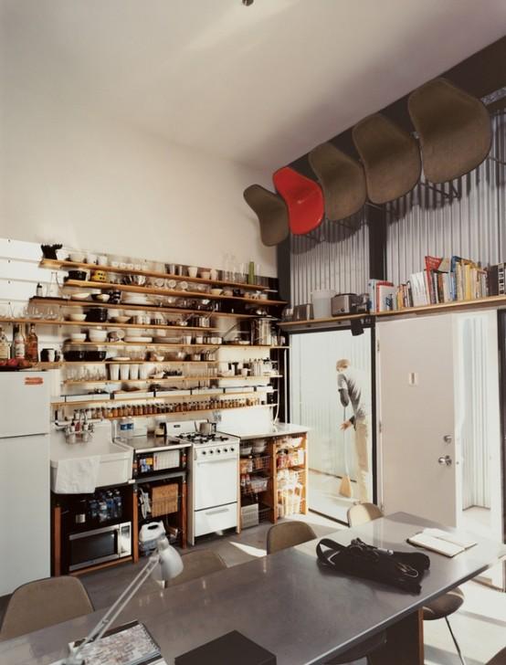 una piccola ma funzionale cucina con armadi a giorno, uno scaffale sovradimensionato che occupa l'intera parete e alcuni elettrodomestici
