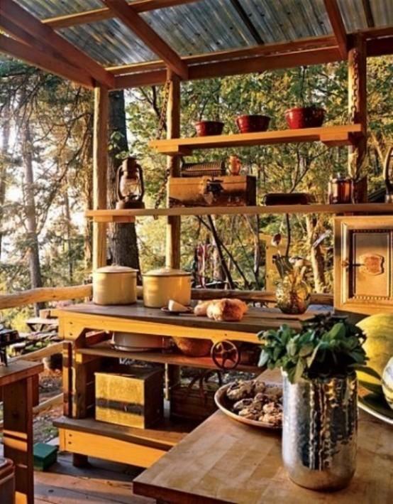 una piccola cucina esterna con armadi in legno e scaffali aperti per godersi il panorama, tocchi di giallo e lanterne a candela