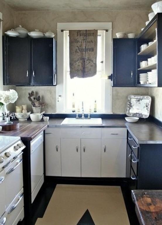 una piccola cucina vintage blu scuro e bianca con ripiani macchiati di scuro e un tappeto geometrico