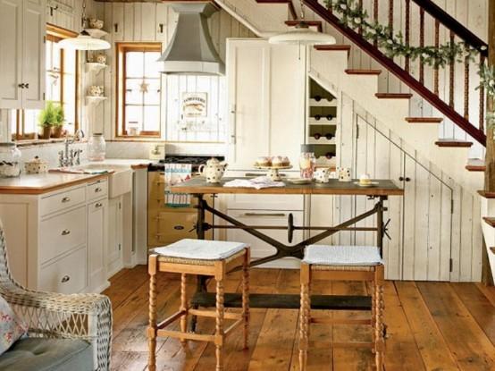 una piccola cucina rustica con armadi bianchi, ripiani macchiati di luce, un tavolo vintage e sgabelli intagliati, lampade a sospensione