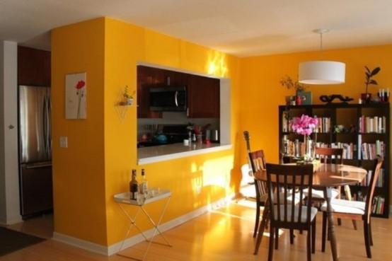 una piccola cucina posta all'interno di un cubo giallo brillante, con una finestra tra la sala da pranzo e un carrello bar e uno scaffale