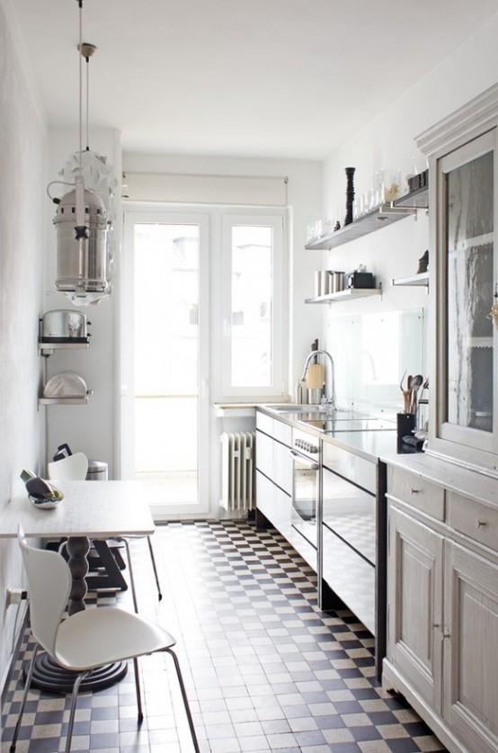 una cucina scandinava vintage in bianco con scaffali aperti e armadi, uno spazio rustico con sedie e un tavolo in legno intagliato più un pavimento a mosaico