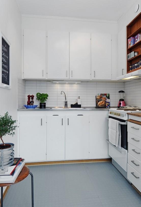 una piccola cucina minimalista in bianco, con alzatina piastrellata, luci e uno sgabello per riporre gli oggetti