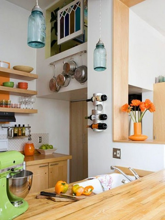 una piccola cucina contemporanea con scaffali aperti e armadi, padelle e pentole tinti di luce attaccati alle pareti
