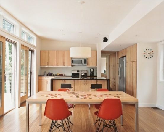 una piccola cucina contemporanea fatta con armadi in legno tinto chiaro, un tavolo e sedie ruggine
