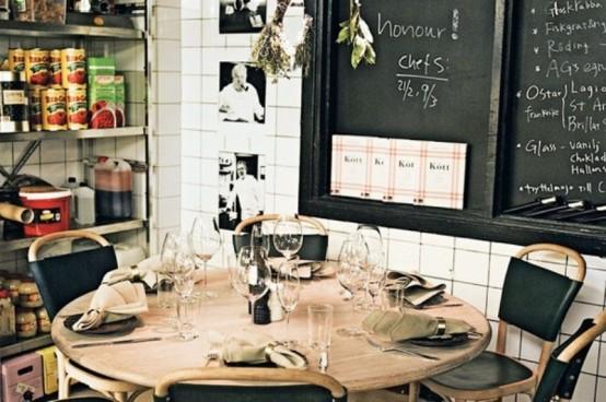 un piccolo spazio industriale mela con un tavolo rotondo in legno, sedie in pelle, scaffali aperti e lavagne
