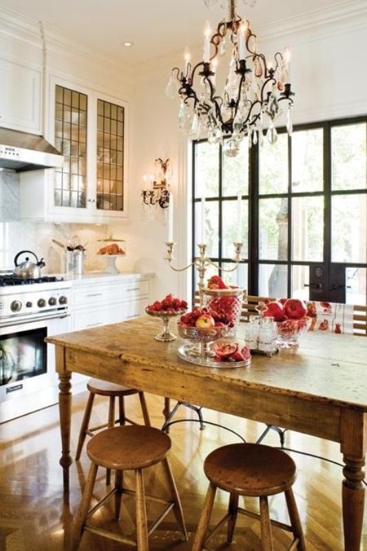 una piccola cucina eclettica con mobili bianchi della fattoria, un set da pranzo in legno vintage e un grande lampadario di cristallo
