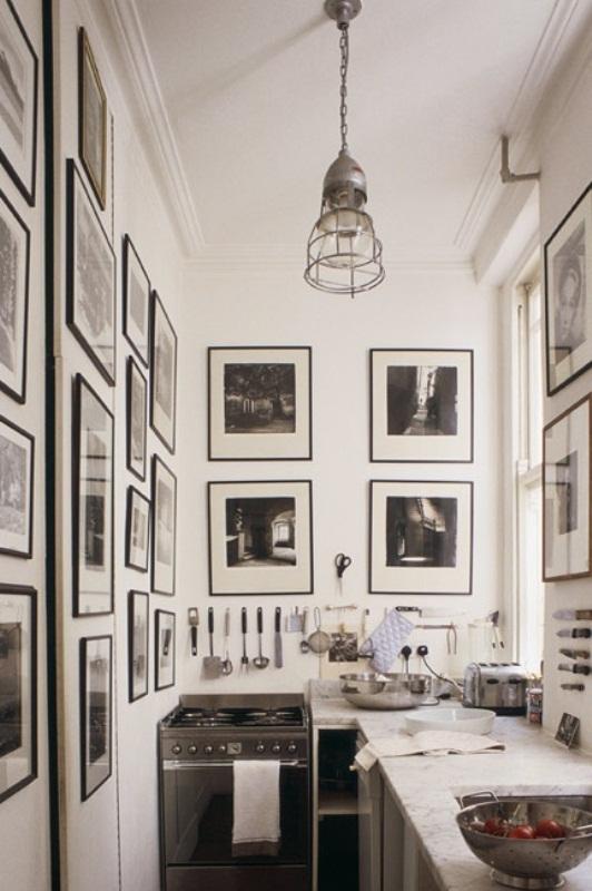 una piccola cucina monocromatica realizzata con armadi e piani di lavoro neutri, foto in bianco e nero alle pareti e una lampada a sospensione