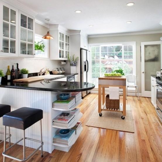 una piccola cucina moderna da fattoria fatta con armadi bianchi, ripiani neri, sgabelli in pelle e un'isola da cucina in legno su ruote