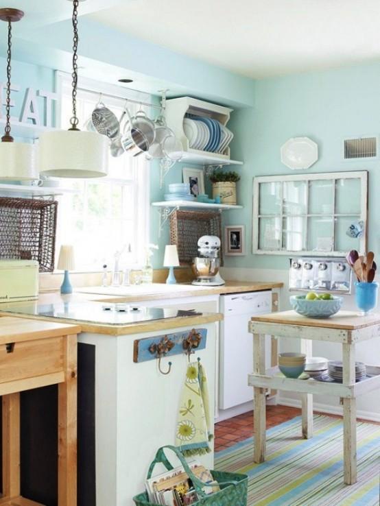 una piccola cucina color acqua di ispirazione vintage con armadi neutri e ripiani colorati chiari, una piccola isola da cucina, scaffali aperti e lampade a sospensione