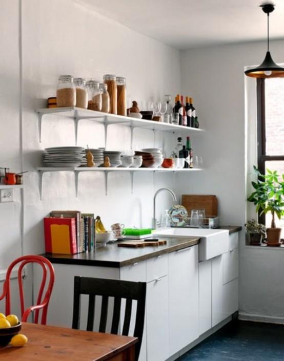 una piccola cucina contemporanea con armadi bianchi, scaffali aperti, una sala da pranzo con sedie non corrispondenti