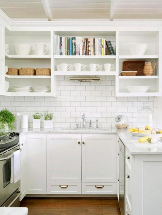 una piccola ma elegante cucina da fattoria in bianco, con hardware dorato, piastrelle bianche della metropolitana e scaffali aperti più cassetti per la conservazione