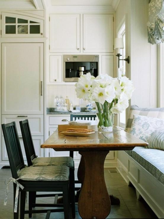 una piccola cucina neutra da fattoria con ripiani grigi, un tavolo in legno, sedie nere e una panca imbottita blu