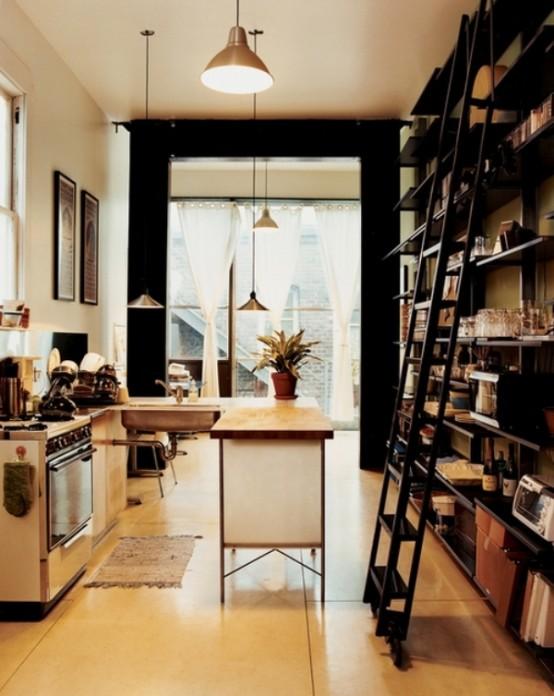 una piccola cucina leggera con isola cucina e armadi a giorno, lampade a sospensione e un grande scaffale a muro con una scala per riporre tutto ciò di cui potresti aver bisogno
