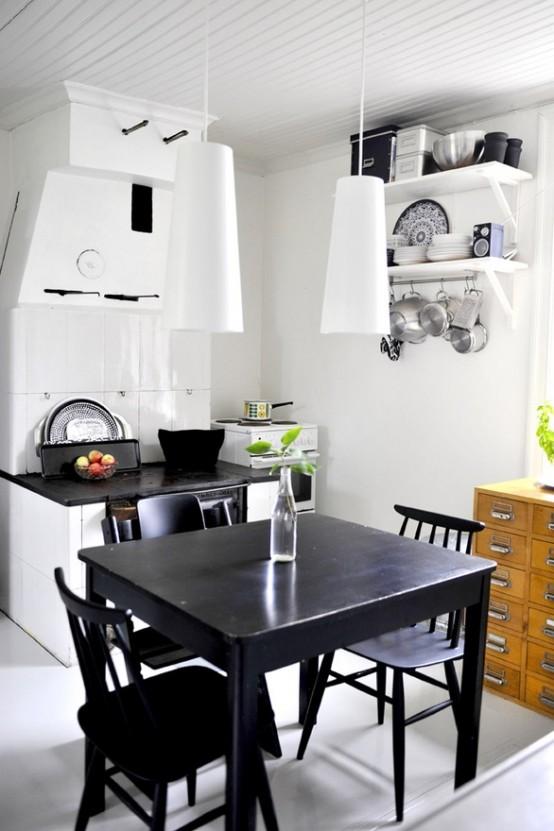 una piccola cucina eclettica con un mobile bianco, un piano di lavoro nero, lampade a sospensione bianche, un set da pranzo nero vintage e un armadietto da farmacia