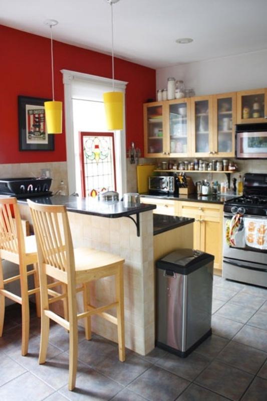 una piccola cucina luminosa con un muro rosso, lampade a sospensione gialle, mobili tinti di luce e un piano di lavoro alto per mangiare