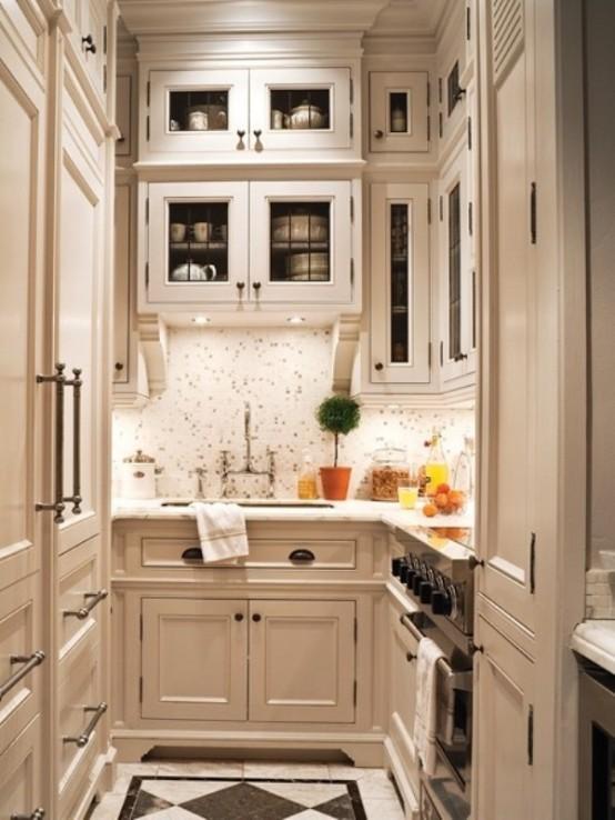 una piccola cucina di ispirazione vintage bianco sporco con molto spazio per riporre i divani, un alzatina in piastrelle e luci aggiuntive per cucinare comodamente