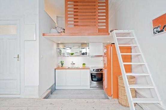 una piccola cucina luminosa con armadi bianchi, un frigorifero arancione brillante, ripiani arancioni e tocchi di lime