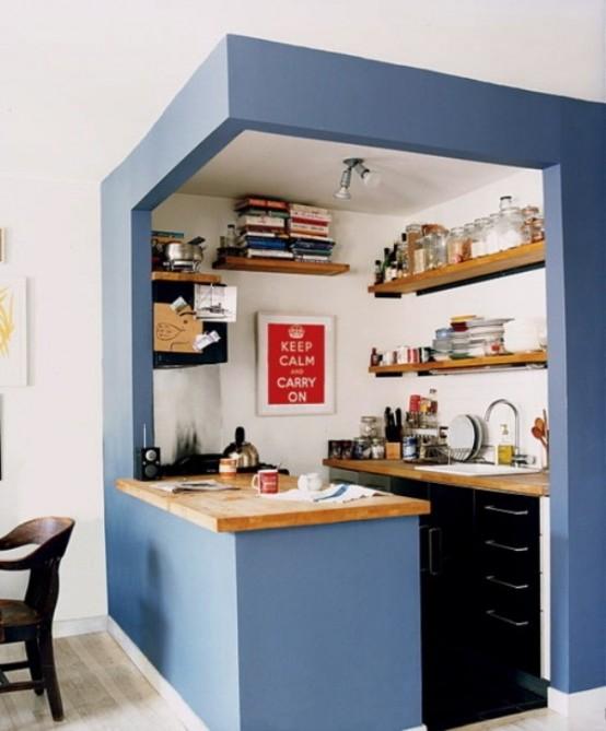 una piccola cucina inserita in un cubo blu, con armadi neri incorporati, ripiani in legno chiaro e scaffali aperti