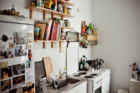 una piccola cucina contemporanea in bianco, con ripiani in legno tinto di luce e molte foto personali