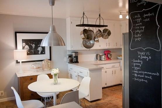 una piccola cucina tutta bianca con un piano di lavoro che separa la zona cucina e pranzo con un tavolo rotondo e sedie