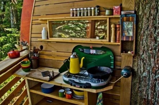 una piccola cucina esterna in legno chiaro, una griglia portatile, una finestra e alcune stoviglie colorate
