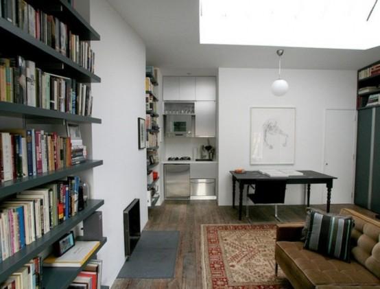 un piccolo angolo cucina minimalista fatto con armadi metallici ed elettrodomestici coordinati proprio nell'angolo dello studio